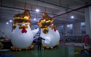 This picture taken on January 6, 2017 shows workers inflating giant chickens resembling Donald Trump in a factory in Jiaxing.  A Chinese factory is hatching giant inflatable chickens resembling Donald Trump to usher in the Year of the Rooster. The five-metre (16-foot) fowls sport the distinctive golden mane of the US president-elect and mimic his signature hand gestures with their tiny wings.  / AFP PHOTO / Johannes EISELE