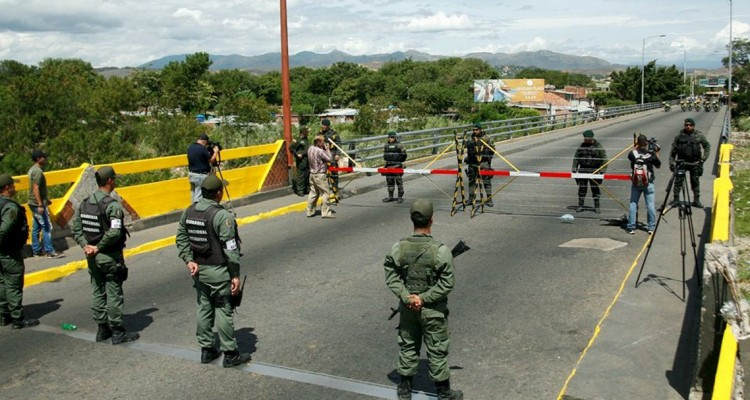 Venezuela's National Guards (bottom) stand in front of Colombia's soldiers at Simon Bolivar international bridge, on the border with Colombia, at San Antonio in Tachira state, Venezuela August 20, 2015. Venezuela's President Nicolas Maduro late Wednesday ordered two border crossings to Colombia closed for 72 hours after a shoot-out left three soldiers injured. The members of the military were attacked during an anti-smuggling operation in the Venezuelan border town of San Antonio in the state of Tachira, according to the government. REUTERS/Carlos Eduardo Ramirez      TPX IMAGES OF THE DAY