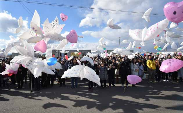 Balloons in the shape of doves are released into the air during a memorial service for victims of the 2011 quake-tsunami disaster in Natori, Miyagi prefecture on March 11, 2017. Japan is marking on March 11 the sixth anniversary of the magnitude 9.0 quake which struck under the Pacific Ocean and the ensuing tsunami which left about 18,500 people dead or missing. The massive flow of water overwhelmed cooling systems at the Fukushima Daiichi plant, causing meltdowns in three of its six reactors in what was the worst nuclear disaster since Chernobyl in 1986. / AFP PHOTO / KAZUHIRO NOGI