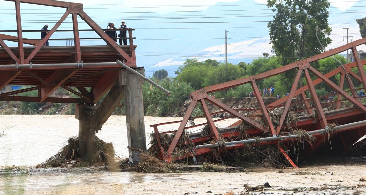 View of the Viru Bridge, which carries the Panamerican Highway between northern Peru and Lima, after it collapsed into the Viru River in the town of Viru due to the intense rains, cutting off supplies to the northern part of the country, on March 19, 2017.  The El Nino climate phenomenon is causing muddy rivers to overflow along the entire Peruvian coast, isolating communities and neighbourhoods. Thousands have been affected since January, and 72 people have died. Most cities face water shortages as water lines have been compromised by mud and debris. / AFP PHOTO / CELSO ROLDAN
