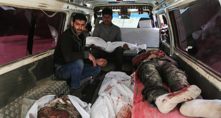 EDITORS NOTE: Graphic content / Syrians transport the body of people killed after a reported air strike in the rebel-controlled town of Hamouria, in the eastern Ghouta region on the outskirts of the capital Damascus, on March 25, 2017.  At least 16 civilians were killed and dozens wounded on March 25, 2017 in an air strike the rebel-held area, the Syrian Observatory for Human Rights monitor said, although it was not immediately clear who was responsible for the strike. / AFP PHOTO / AMER ALMOHIBANY