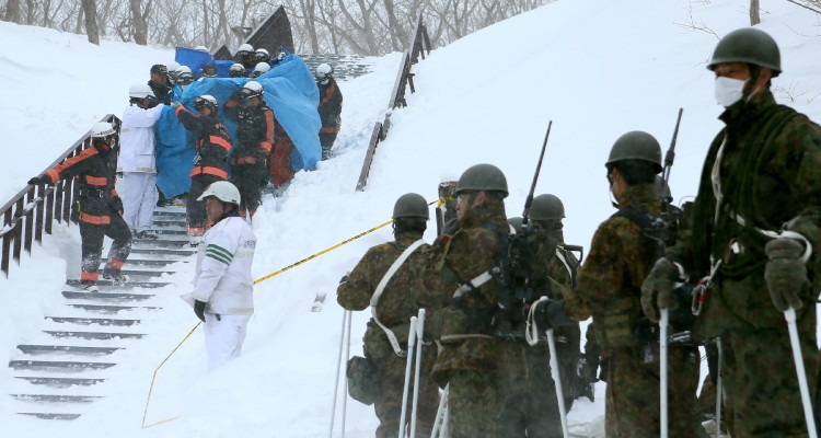 Firefighters carry a survivor they rescued from the site of an avalanche in Nasu town, Tochigi prefecture on March 27, 2017, while Self Defense Force personnel look on.  Eight high school students were feared dead on March 27 after being engulfed by an avalanche while on a mountain-climbing outing with dozens of others, officials said. / AFP PHOTO / JIJI PRESS / JIJI PRESS / Japan OUT