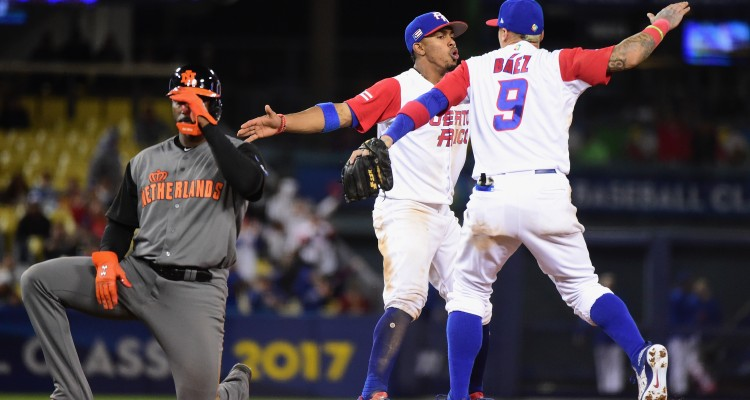 LOS ANGELES, CA - MARCH 20: Francisco Lindor #12 and Javier Baez #9 of the Puerto Rico celebrate an inning-ending double play in the 11th as Yurendell Decaster #7 of the Netherlands reacts during Game 1 of the Championship Round of the 2017 World Baseball Classic at Dodger Stadium on March 20, 2017 in Los Angeles, California.   Harry How/Getty Images/AFP