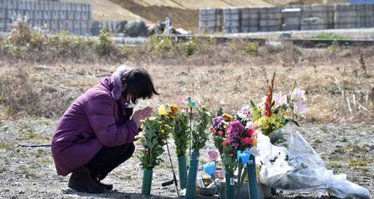 A woman prays for victims of the 2011 quake-tsunami disaster in Namie, a no entry zone in Fukushima prefecture on March 11, 2017.  Japan is marking on March 11 the sixth anniversary of the magnitude 9.0 quake which struck under the Pacific Ocean and the ensuing tsunami which left about 18,500 people dead or missing. / AFP PHOTO / KAZUHIRO NOGI