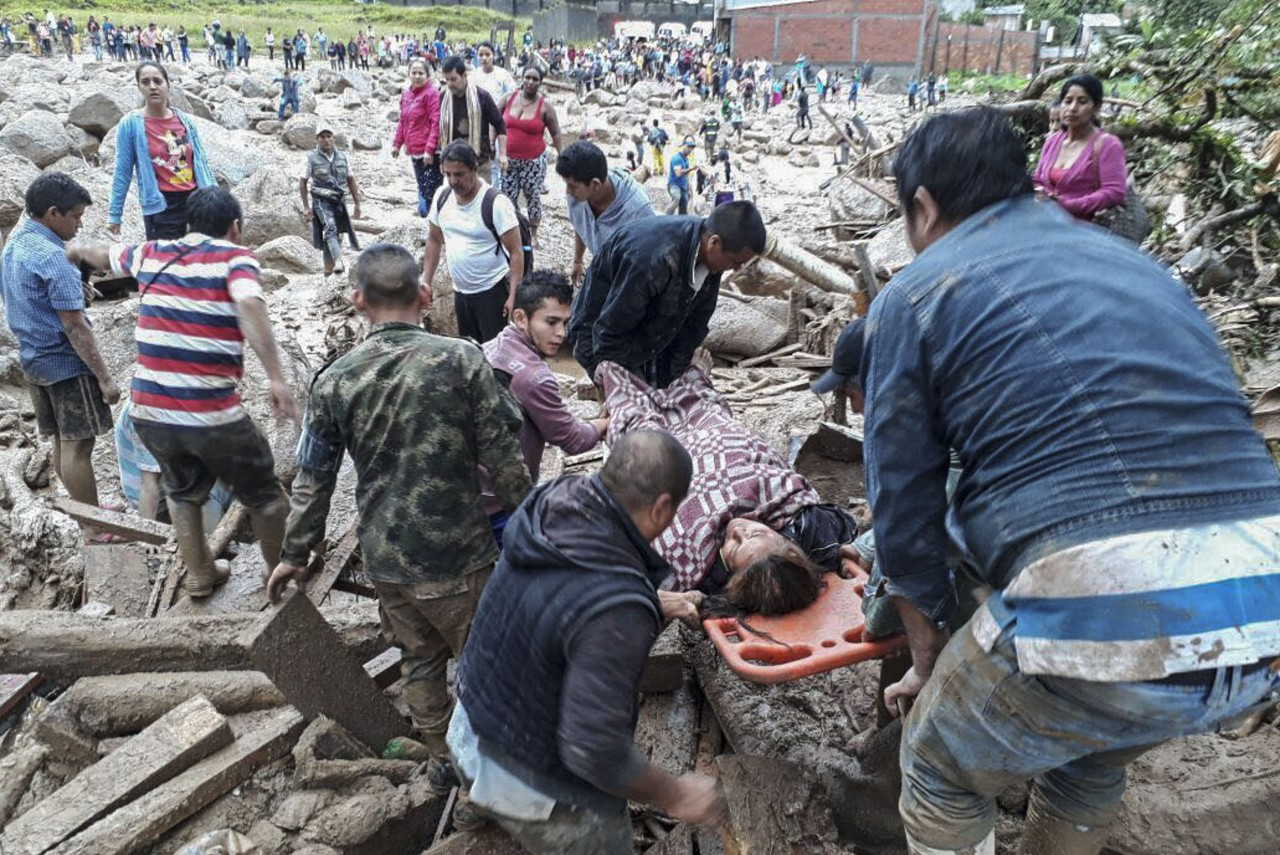 Handout picture released by the Colombian Army press office showing people helping to carry a woman after mudslides following heavy rains, in Mocoa, Putumayo department, on April 1, 2017. Mudslides in southern Colombia -caused by the rise of the Mocoa River and three tributaries- have claimed at least 16 lives and injured some 65 people following recent torrential rains, the authorities said. / AFP PHOTO / EJERCITO DE COLOMBIA / HO / RESTRICTED TO EDITORIAL USE - MANDATORY CREDIT AFP PHOTO / EJERCITO DE COLOMBIA - NO MARKETING - NO ADVERTISING CAMPAIGNS - DISTRIBUTED AS A SERVICE TO CLIENTS