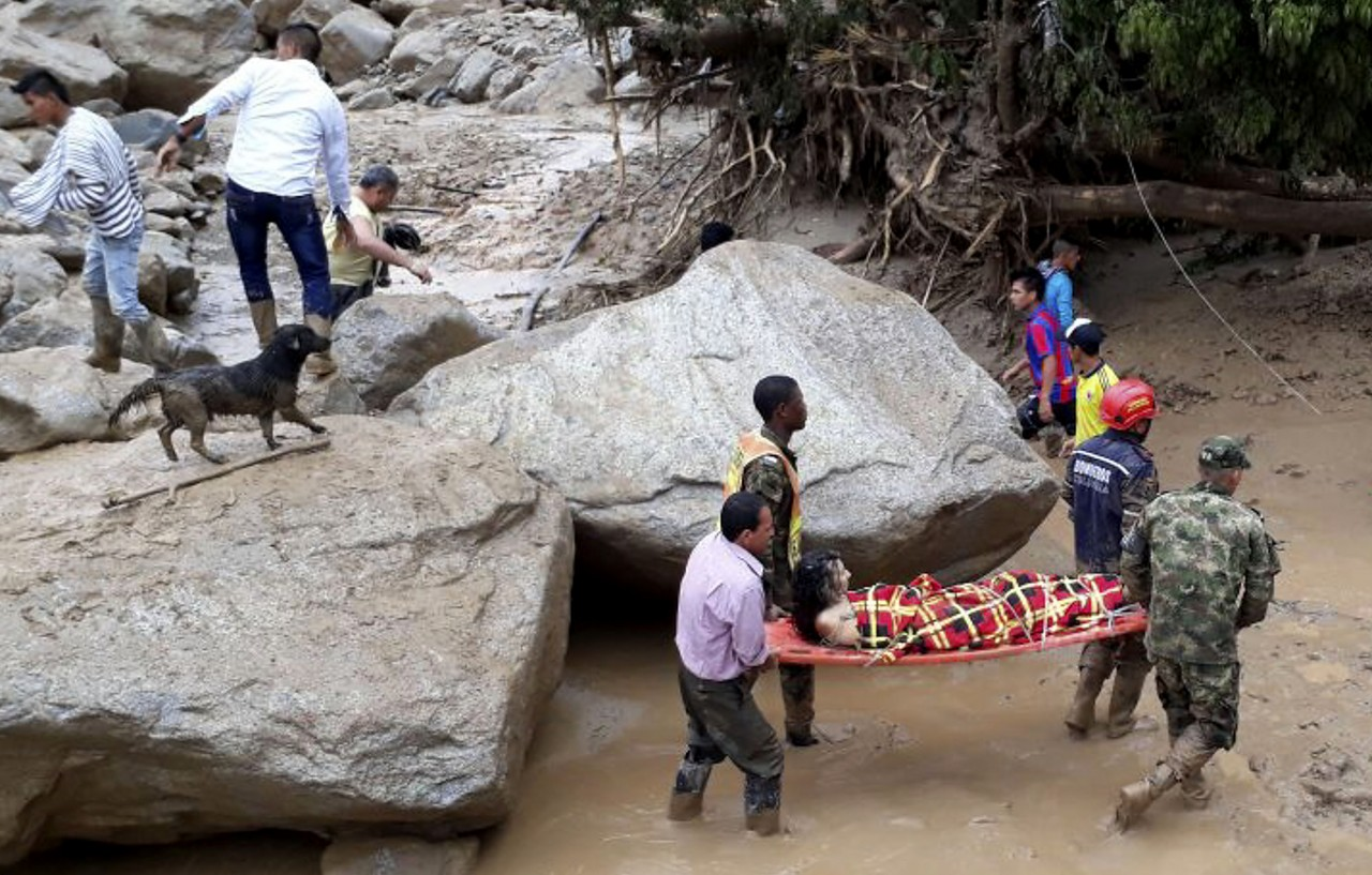 Handout picture released by the Colombian Army press office showing rescuers carrying a woman after mudslides caused by heavy rains, in Mocoa, Putumayo department, on April 1, 2017. Mudslides in southern Colombia -caused by the rise of the Mocoa River and three tributaries- have claimed at least 16 lives and injured some 65 people following recent torrential rains, the authorities said. / AFP PHOTO / EJERCITO DE COLOMBIA / HO / RESTRICTED TO EDITORIAL USE - MANDATORY CREDIT AFP PHOTO / EJERCITO DE COLOMBIA - NO MARKETING - NO ADVERTISING CAMPAIGNS - DISTRIBUTED AS A SERVICE TO CLIENTS