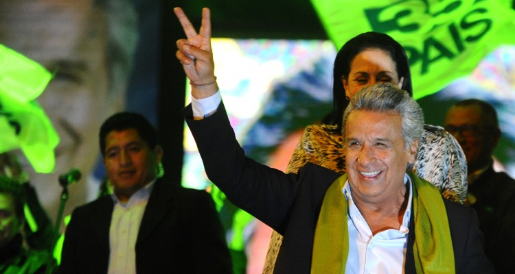 "The Ecuadorean presidential candidate of the ruling Alianza PAIS party, Lenin Moreno, gives the ""V for victory"" sign to his supporters as they wait for the final results of the runoff election, in Quito on April 2, 2017. / AFP PHOTO / JUAN RUIZ"
