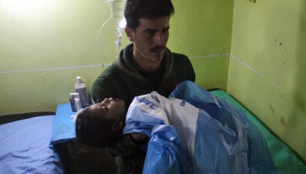 An unconscious Syrian child is carried at a hospital in Khan Sheikhun, a rebel-held town in the northwestern Syrian Idlib province, following a suspected toxic gas attack on April 4, 2017.  A suspected chemical attack killed at least 58 civilians including several children in rebel-held northwestern Syria, a monitor said, with the opposition accusing the government and demanding a UN investigation. / AFP PHOTO / Omar haj kadour