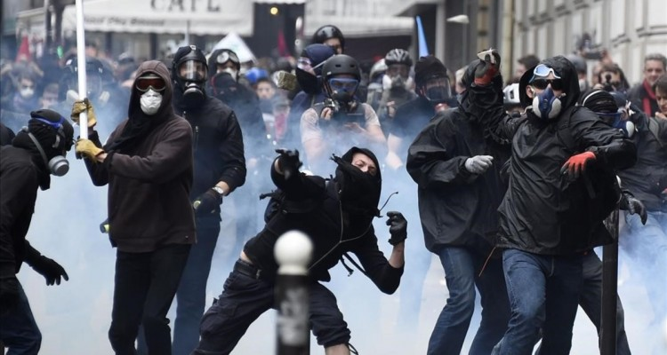 Masked protesters throw stones during a demonstration against proposed labour reforms in Paris on June 14  2016   Several hundred masked protesters hurled objects at police on June 14 during a demonstration in Paris against a contested reform of French labour laws  authorities said    AFP PHOTO   DOMINIQUE FAGET