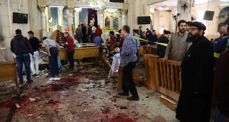 EDITORS NOTE: Graphic content / A general view shows people looking at the aftermath following a bomb blast which struck worshippers gathering to celebrate Palm Sunday at the Mar Girgis Coptic Church in the Nile Delta City of Tanta, 120 kilometres (75 miles) north of Cairo, on April 9, 2017. / AFP PHOTO / STRINGER