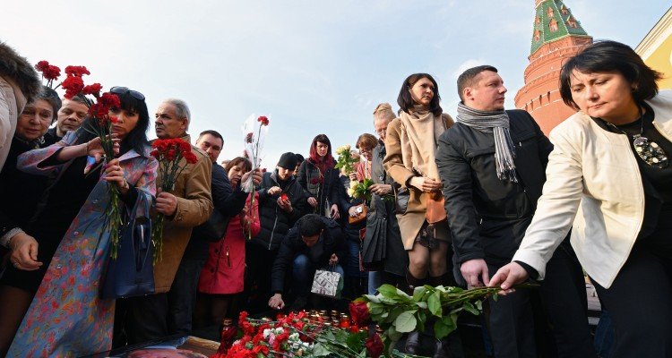 People place flowers in honour of the victims of April 3 blast in the Saint Petersburg metro at a memorial stone reading Leningrad by the Kremlin wall during a commemorative event in central Moscow on April 6, 2017. / AFP PHOTO / Natalia KOLESNIKOVA