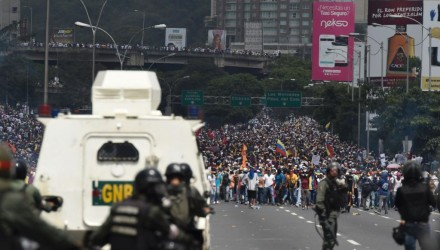Demonstrators are confronted by the riot police during a rally against Venezuelan President Nicolas Maduro, in Caracas on April 19, 2017. Clashes broke out Wednesday at massive protests against Maduro, as riot police fired tear gas to push back stone-throwing demonstrators and a young protester was shot dead. Violence erupted when thousands of opposition protesters tried to march on central Caracas, a pro-government bastion where red-clad Maduro supporters were massing for a counter-demonstration.  / AFP PHOTO / Juan BARRETO