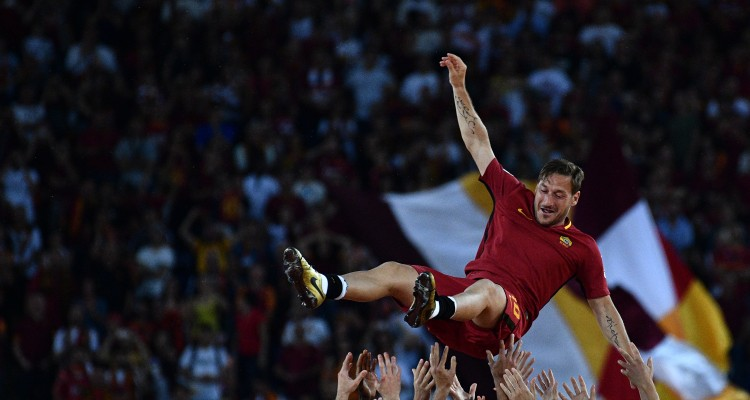 Roma's Captain Francesco Totti is tossed in the air by his teammates during a ceremony following his last match with AS Roma after the Italian Serie A football match AS Roma vs Genoa on May 28, 2017 at the Olympic Stadium in Rome. Italian football icon Francesco Totti retired from Serie A after 25 seasons with Roma, in the process joining a select group of 'one-club' players. / AFP PHOTO / Vincenzo PINTO