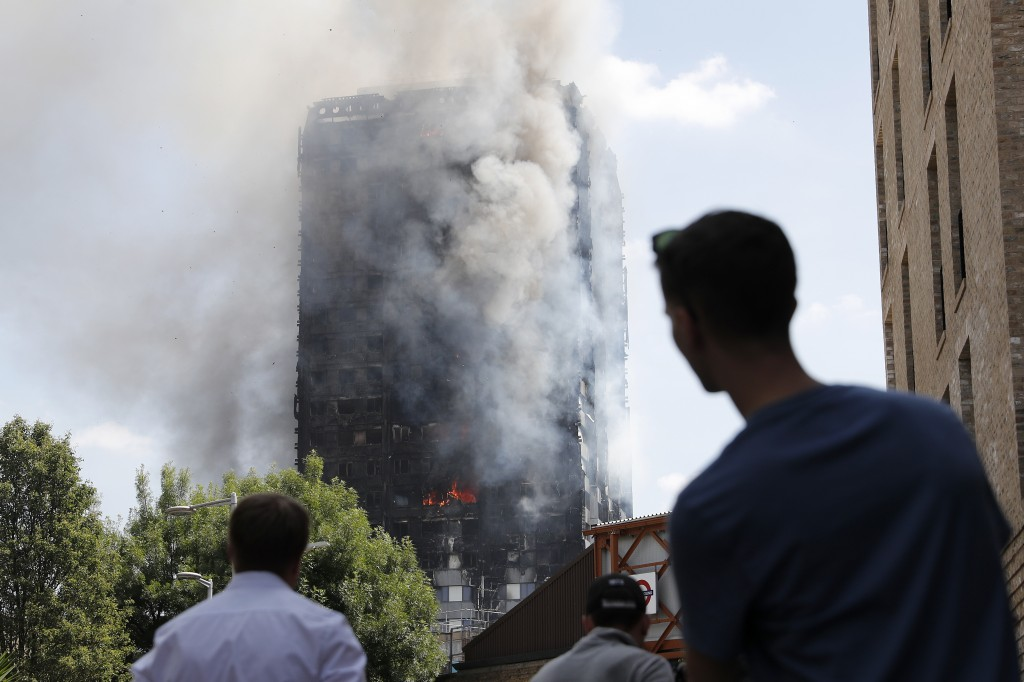 Pedestrians look up towards Grenfell Tower, a residential block of flats in west London on June 14, 2017, as firefighters continue to control a fire that engulfed the building in the early hours of the morning. Shaken survivors of a blaze that ravaged a west London tower block told Wednesday of seeing people trapped or jump to their doom as flames raced towards the building's upper floors and smoke filled the corridors. / AFP PHOTO / Adrian DENNIS