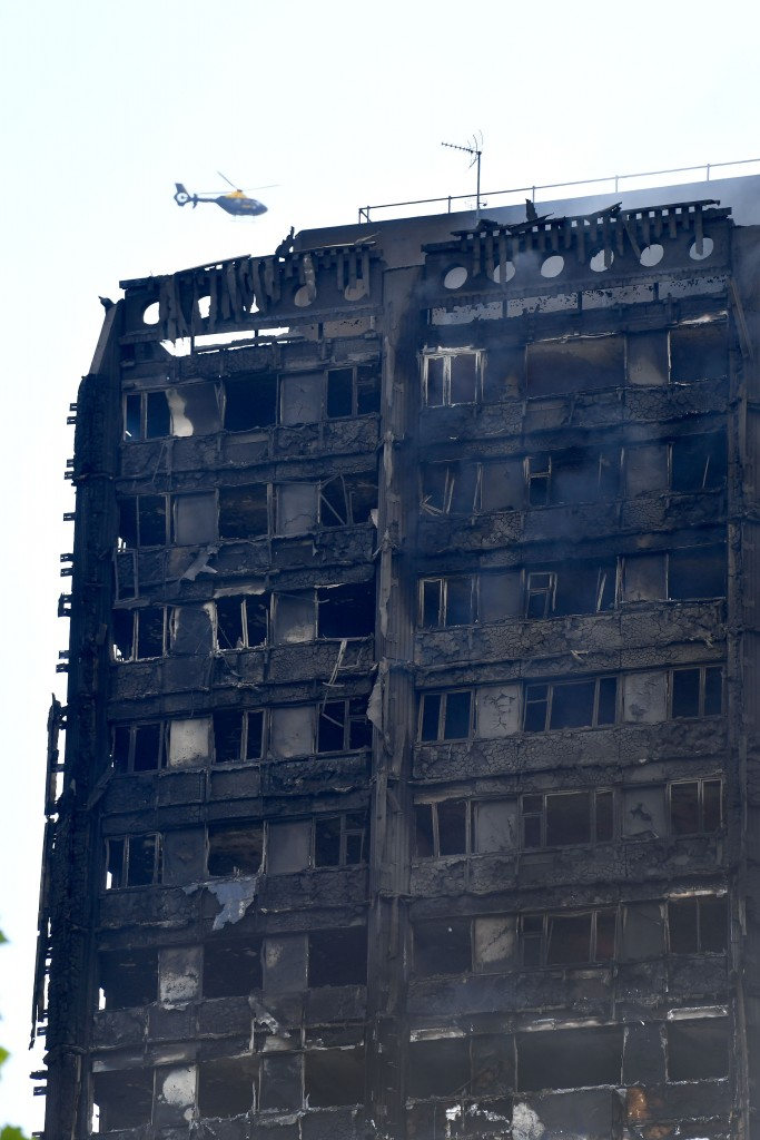 A helicopter hovers near the burnt-out facade of Grenfell Tower after a fire ripped through the building in west London on June 14, 2017. At least six people were killed Wednesday when a massive fire tore through a London apartment block overnight, with survivors voicing anger over longstanding safety fears at the 24-storey Grenfell Tower. / AFP PHOTO / Ben STANSALL