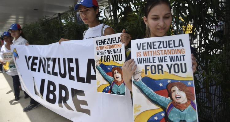 Members of the Venezuelan community in Mexico stage a protest against the Venezuelan government on the eve of the opening of 47th General Assembly of the Organization of American States (OAS or OEA in Spanish), outside the international airport in Cancun, Mexico on June 18, 2017. / AFP PHOTO / PEDRO PARDO