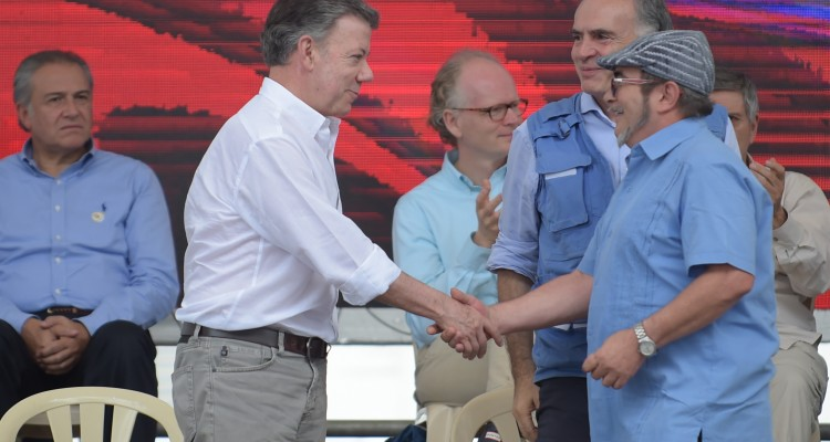 "FARC rebel leader Rodrigo Londono Echeverri, known as ""Timochenko""(R), Colombian president Juan Manuel Santos (L) and the UN Secretary-General's Special Representative for Colombia and Head of the UN Mission to Colombia, Jean Arnault (C) attend the final act of abandonment of arms and its end as an armed group at Transitional Standardization Zone Mariana Paez, Buena Vista, Mesetas municipality, Colombia on June 27, 2017. / AFP PHOTO / RAUL ARBOLEDA"