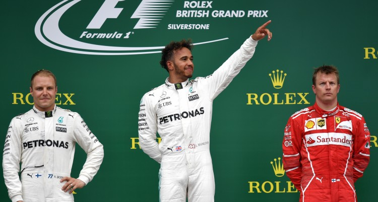 Winner Mercedes' British driver Lewis Hamilton (C) celebrates on the podium next to second placed Mercedes' Finnish driver Valtteri Bottas (L) and third placed Ferrari's Finnish driver Kimi Raikkonen after the British Formula One Grand Prix at the Silverstone motor racing circuit in Silverstone, central England on July 16, 2017. / AFP PHOTO / Andrej ISAKOVIC