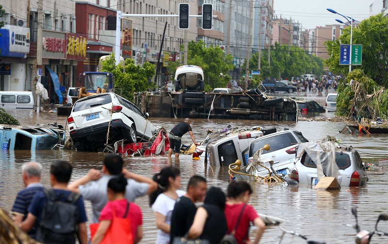 This photo taken on July 14, 2017 shows people looking at submerged cars in a flooded street in Yongji, a county under the administration of the city of Jilin in northeast China's Jilin province. Heavy rains caused flooding that left 18 people dead and another 18 missing around Jilin, with more than 110,000 evacuated when flooding hit the city on July 13 and 14. / AFP PHOTO / STR / China OUT