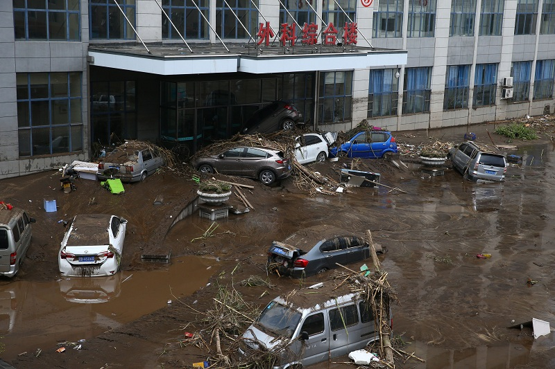 This photo taken on July 14, 2017 shows submerged cars in a flooded street in Yongji, a county under the administration of the city of Jilin in northeast China's Jilin province. Heavy rains caused flooding that left 18 people dead and another 18 missing around Jilin, with more than 110,000 evacuated when flooding hit the city on July 13 and 14. / AFP PHOTO / STR / China OUT