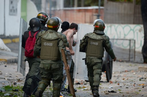 National Guard personnel in riot gear arrest an opposition demonstrator during clashes ensuing an anti-government protest in Caracas, on July 26, 2017. Venezuelans blocked off deserted streets Wednesday as a 48-hour opposition-led general strike aimed at thwarting embattled President Nicolas Maduro's controversial plans to rewrite the country's constitution got underway. / AFP PHOTO / Federico Parra