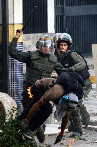 National Guard riot police and opposition demonstrators clash ensuing an anti-government protest in Caracas, on July 26, 2017. Venezuelans blocked off deserted streets Wednesday as a 48-hour opposition-led general strike aimed at thwarting embattled President Nicolas Maduro's controversial plans to rewrite the country's constitution got underway. / AFP PHOTO / FEDERICO PARRA