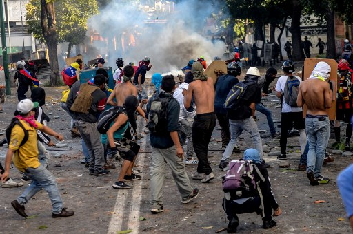 Opposition demonstrators skirmish with riot police ensuing an anti-government protest in Caracas, on July 26, 2017. Venezuelans blocked off deserted streets Wednesday as a 48-hour opposition-led general strike aimed at thwarting embattled President Nicolas Maduro's controversial plans to rewrite the country's constitution got underway. / AFP PHOTO / FEDERICO PARRA