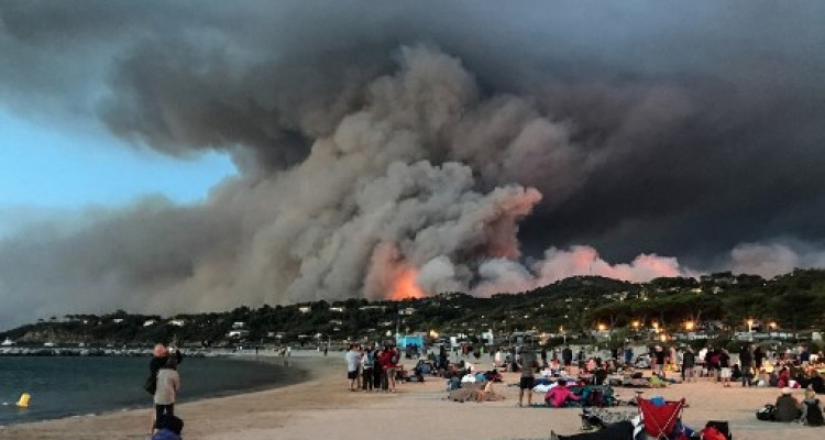 Evacuated people take refuge on the beach and look at a fire burning the forest in Bormes-les-Mimosas, southern France, at sunrise on July 26, 2017. Over 10,000 people, including thousands of holidaymakers, were evacuated from campsites and homes in southern France as firefighters on July 26, 2017 battled the latest in a string of huge blazes along the Mediterranean coast. / AFP PHOTO / Marion LEFLOUR