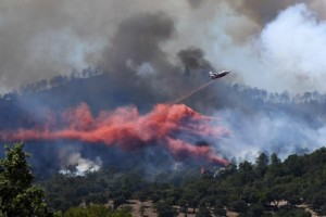 A fire fighting Canadair aircraft drops fire retardant over a fire near Bormes-les-Mimosas, southeastern France, on July 26, 2017. At least 10,000 people, including thousands of holidaymakers, were evacuated overnight after a new wildfire broke out in southern France, which was already battling massive blazes, authorities said on July 26. / AFP PHOTO / Anne-Christine POUJOULAT