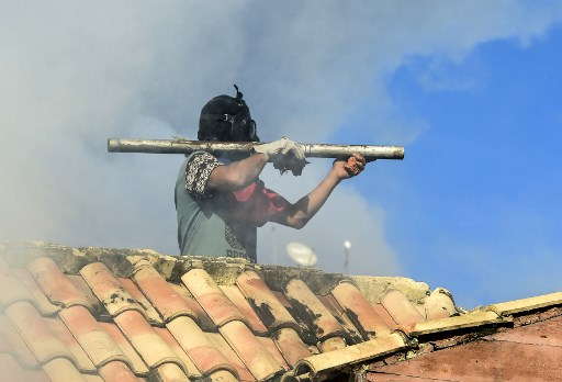 An opposition demonstrator on a roof aims a makeshift firecracker launcher at riot police during clashes ensuing an anti-government protest in Caracas, on July 26, 2017. Venezuelans blocked off deserted streets Wednesday as a 48-hour opposition-led general strike aimed at thwarting embattled President Nicolas Maduro's controversial plans to rewrite the country's constitution got underway. / AFP PHOTO / RONALDO SCHEMIDT