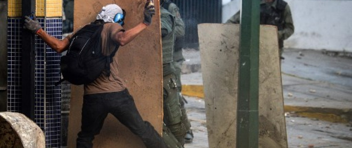 Opposition demonstrators clash with riot police ensuing an anti-government protest in Caracas, on July 26, 2017. Venezuelans blocked off deserted streets Wednesday as a 48-hour opposition-led general strike aimed at thwarting embattled President Nicolas Maduro's controversial plans to rewrite the country's constitution got underway. / AFP PHOTO / FEDERICO PARRA