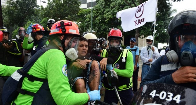 A wounded anti-government activist is assisted by medics during clashes with the police which erupted during a protest against the elections for a Constituent Assembly in Caracas on July 30, 2017. Deadly violence erupted around the controversial vote, with a candidate to the all-powerful body being elected shot dead and troops firing weapons to clear protesters in Caracas and elsewhere. / AFP PHOTO / Ronaldo SCHEMIDT