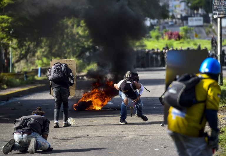 Anti-government activists skirmish with riot police during a protest against the election of a Constituent Assembly proposed by Venezuelan President Nicolas Maduro, in Caracas on July 30, 2017. Deadly violence erupted around the controversial vote, with a candidate to the all-powerful body being elected shot dead and troops firing weapons to clear protesters in Caracas and elsewhere. / AFP PHOTO / RONALDO SCHEMIDT