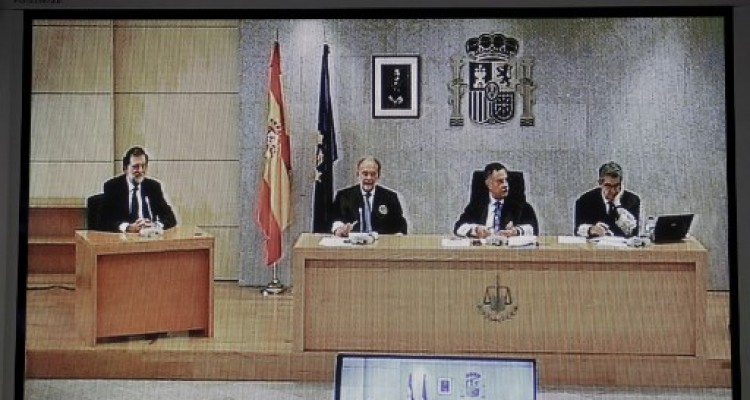 Photo taken from the court house press room of a TV transmitting images of Spanish Prime Minister Mariano Rajoy (L) declaring as a witness beside magistrates Angel Hurtado (C), Julio de Diego Lopez (2L) and Jose Ricardo de Prada in a major graft trial involving members of his conservative Popular Party at Spain's High Court in San Fernando de Henares near Madrid on July 26, 2017. The so-called Gurtel trial centres on a vast kickbacks scheme that allegedly helped finance Rajoy's Popular Party (PP), which today has been weakened by repeated accusations of graft.   / AFP PHOTO / POOL / Chema Moya