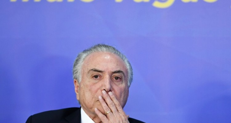 Brazilian President Michel Temer looks on during the announcement of the launching of a new medical college, at Planalto Palace in Brasilia, on August 1, 2017. Brazil's lower house of Congress is set to vote on Wednesday on whether to put Temer on trial for corruption, threatening the country with its second leadership crisis in a year. Temer, a deeply unpopular veteran of the center-right PMDB party, is accused of taking bribes from a meatpacking industry executive.  / AFP PHOTO / EVARISTO SA