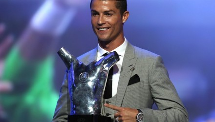 "Real Madrid's Portuguese forward Cristiano Ronaldo gestures as he poses with the trophy after he was awarded the title of ""Best Men's Player in Europe"" at the conclusion of the UEFA Champions League group stage draw ceremony in Monaco on August 24, 2017.  / AFP PHOTO / VALERY HACHE"