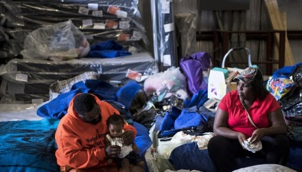 A family rests in a shelter at a Gallery Furniture store during the aftermath of Hurricane Harvey on August 30, 2017 in Houston, Texas. Monster storm Harvey made landfall again Wednesday in Louisiana, evoking painful memories of Hurricane Katrina's deadly strike 12 years ago, as time was running out in Texas to find survivors in the raging floodwaters. / AFP PHOTO / Brendan Smialowski