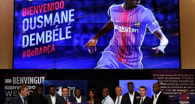 Barcelona's new player Ousmane Dembele (5thL) poses with his new jersey next to Barcelona's president Josep Maria Bartomeu (4thL) and Dembele's relatives at the Camp Nou stadium in Barcelona, during his official presentation at the Catalan football club, on August 28, 2017. French starlet Ousmane Dembele agreed a five-year deal with Barcelona worth 105 million euros ($125 million) plus add-ons. Dembele, 20, moves from Borussia Dortmund, where he has been suspended since he boycotted training on August 10 in protest after the German club rejected Barca's first bid.  / AFP PHOTO / LLUIS GENE