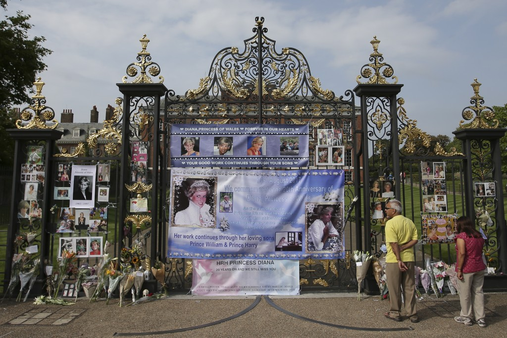 Visitors look at photographs of Diana, Princess of Wales, and floral tributes left outside Kensington Palace in Central London on August 29, 2017 ahead of the 20th anniversary of Princess Diana's death. Britain prepares to mark the twentieth anniversary of the death of Diana, Princess of Wales. August 31, 1997, Britain's Diana, Princess of Wales, died in a high-speed car crash in Paris. For the week following, leading up to her spectacular funeral, Britain was plunged into an unprecedented outpouring of popular grief which shook the monarchy.  / AFP PHOTO / Daniel LEAL-OLIVAS