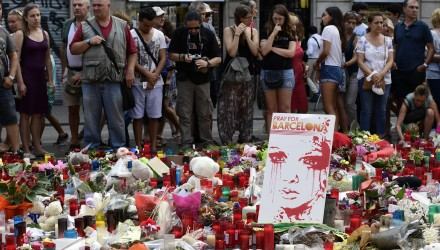 People stand next to flowers, candles and other items set up on the Las Ramblas boulevard in Barcelona as they pay tribute to the victims of the Barcelona attack, three days after a van ploughed into the crowd, killing 13 persons and injuring over 100 on August 20, 2017.  Drivers have ploughed on August 17, 2017 into pedestrians in two quick-succession, separate attacks in Barcelona and another popular Spanish seaside city, leaving 14 people dead and injuring more than 100 others. In the first incident, which was claimed by the Islamic State group, a white van sped into a street packed full of tourists in central Barcelona on Thursday afternoon, knocking people out of the way and killing 13 in a scene of chaos and horror. Some eight hours later in Cambrils, a city 120 kilometres south of Barcelona, an Audi A3 car rammed into pedestrians, injuring six civilians -- one of them critical -- and a police officer, authorities said. / AFP PHOTO / JAVIER SORIANO