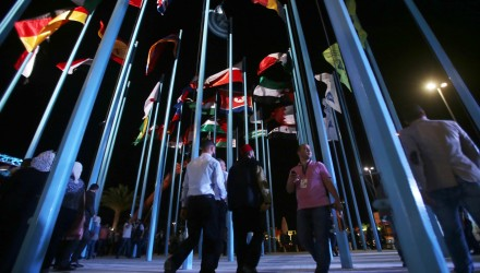 Participants and visitors walk past flags of various countries during the opening of the Damascus International Fair late on August 17, 2017, in the Syrian capital. / AFP PHOTO / Youssef KARWASHAN