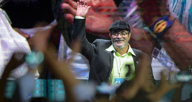 """FARC leader Rodrigo Londono Echeverri, known as """"Timochenko"""", waves during the opening of their National Congress in Bogota on August 27, 2017 Colombia's leftist FARC rebels sought political rebirth on Sunday as they launched steps to transform into a party and seek elected office after disarming to end a half-century war. / AFP PHOTO / Raul Arboleda"""