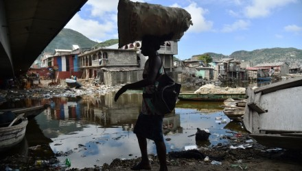 A woman walks next to the Mapou River, in Shadaa neighborhood, in Cap-Haitien, in the north of Haiti, 240 km from Port-au-Prince, ahead of Hurricane Irma on September 5, 2017. The monster hurricane coming on the heels of Harvey, which struck Texas and Louisiana late last month, is expected to hit a string of Caribbean islands including Guadeloupe late Tuesday before heading to Haiti and Florida. The Miami-based National Hurricane Center said Irma had strengthened to the most powerful Category Five, packing winds of 180 miles (280 kilometers) per hour.  / AFP PHOTO / HECTOR RETAMAL