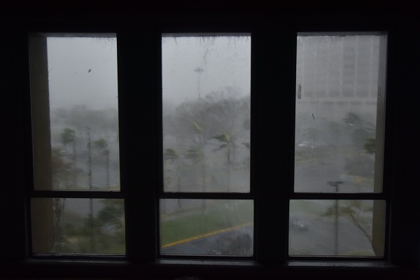 """Rain and wind hit a parking lot at Roberto Clemente Coliseum in San Juan, Puerto Rico, on September 20, 2017, during the passage of the Hurricane Maria. Maria made landfall on Puerto Rico on Wednesday, pummeling the US territory after already killing at least two people on its passage through the Caribbean. The US National Hurricane Center warned of """"large and destructive waves"""" as Maria came ashore near Yabucoa on the southeast coast. / AFP PHOTO / HECTOR RETAMAL"""