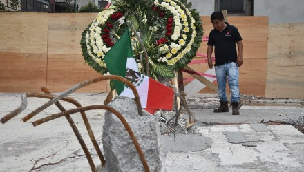 A wreath was placed to honor the the dead on the site where a building was flattened by a strong 7.1-magnitude quake four days ago in Mexico City on September 23, 2017.  In the capital, the quake toppled 39 buildings, mostly in a central area with older construction that is popular with tourists and foreigners living in the city, and also in the south. / AFP PHOTO / YURI CORTEZ