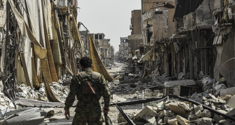 A member of the Syrian Democratic Forces (SDF) walks through the debris in the old city centre on the eastern frontline of Raqa on September 25, 2017. Syrian fighters, backed by US special forces, are battling to clear the last remaining Islamic State (IS) group fighters holed up in their crumbling stronghold of Raqa. / AFP PHOTO / BULENT KILIC