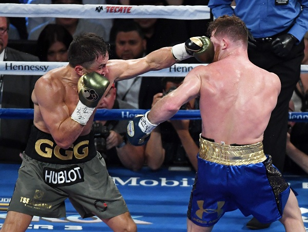 LAS VEGAS, NV - SEPTEMBER 16: Gennady Golovkin (L) thows a left at Canelo Alvarez in the fourth round of their WBC, WBA and IBF middleweight championship bout at T-Mobile Arena on September 16, 2017 in Las Vegas, Nevada. The boxers fought to a draw and Golovkin retained his titles.   Ethan Miller/Getty Images/AFP
