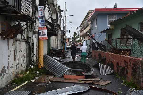 Men walk past damaged homes after the passage of Hurricane Maria, in San Juan, Puerto Rico, on September 20, 2017. Maria slammed into Puerto Rico on, cutting power on most of the US territory as terrified residents hunkered down in the face of the island's worst storm in living memory. After leaving a deadly trail of destruction on a string of smaller Caribbean islands, Maria made landfall on Puerto Rico's southeast coast around daybreak, packing winds of around 150mph (240kph).  / AFP PHOTO / Hector RETAMAL