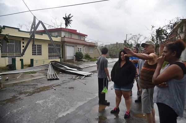 Inhabitants of Puerto Nuevo neighbourhood stand next to roof blown off during the passage of Hurricane Maria, in San Juan, Puerto Rico, on September 20, 2017. Maria slammed into Puerto Rico on, cutting power on most of the US territory as terrified residents hunkered down in the face of the island's worst storm in living memory. After leaving a deadly trail of destruction on a string of smaller Caribbean islands, Maria made landfall on Puerto Rico's southeast coast around daybreak, packing winds of around 150mph (240kph).  / AFP PHOTO / HECTOR RETAMAL
