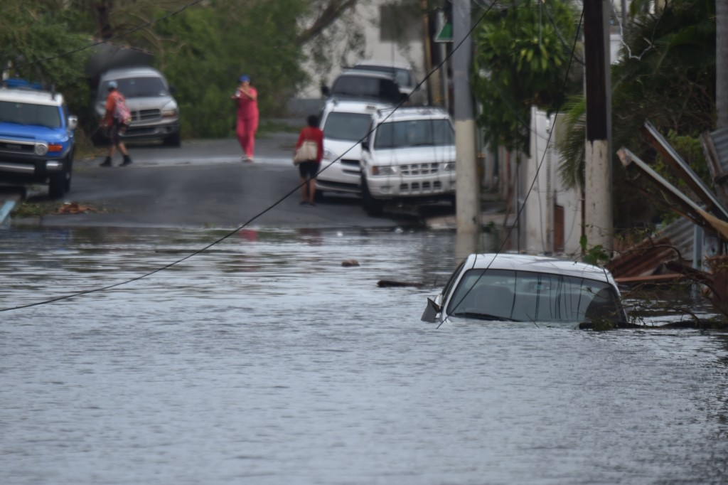 """A car is viewed stuck in a flooded street in Santurce, in San Juan, Puerto Rico, on September 21, 2017.  Puerto Rico braced for potentially calamitous flash flooding on Thursday after being pummeled by Hurricane Maria which devastated the island and knocked out the entire electricity grid. The hurricane, which Puerto Rico Governor Ricardo Rossello called """"the most devastating storm in a century,"""" had battered the island of 3.4 million people after roaring ashore early Wednesday with deadly winds and heavy rain.  / AFP PHOTO / HECTOR RETAMAL"""